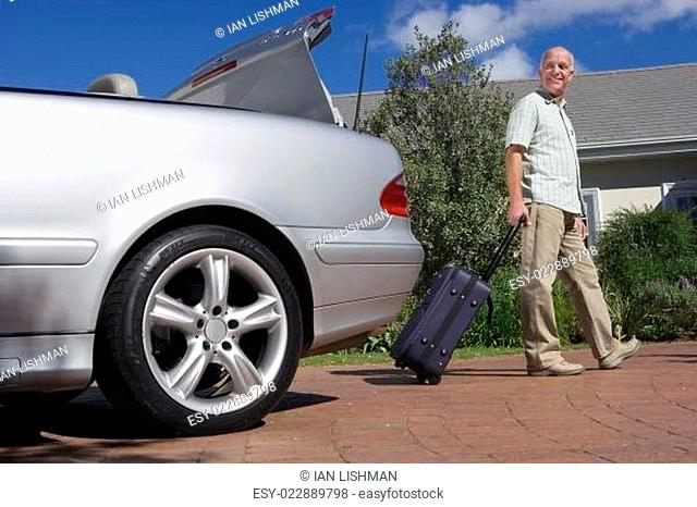Senior man pulling suitcase on wheels from parked car boot on driveway, smiling, side view, portrait (surface level)