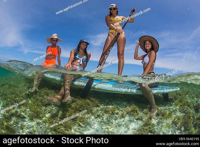 Four Beautiful Girls With Paddle Board enjoying travel and Vacation on Caribbean beach with turquoise water sea. Fifty fifty Photography