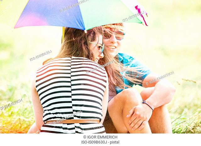 Young couple with umbrella relaxing in field
