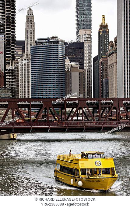 A water taxi travels the Chicago River by State Street in Chicago, IL