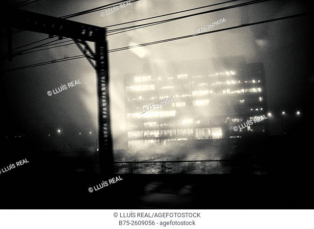 Urban shoot of a apartment building seen through a window of a train at dusk in a foggy day. London, England, UK, Europe
