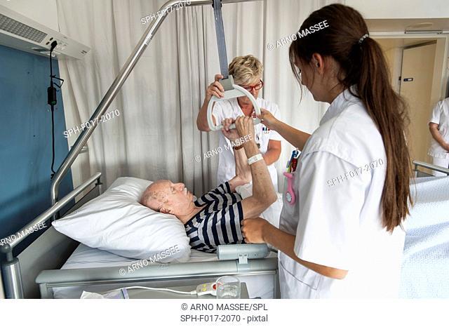 MODEL RELEASED. Female nurses assisting senior male patient in hospital bed