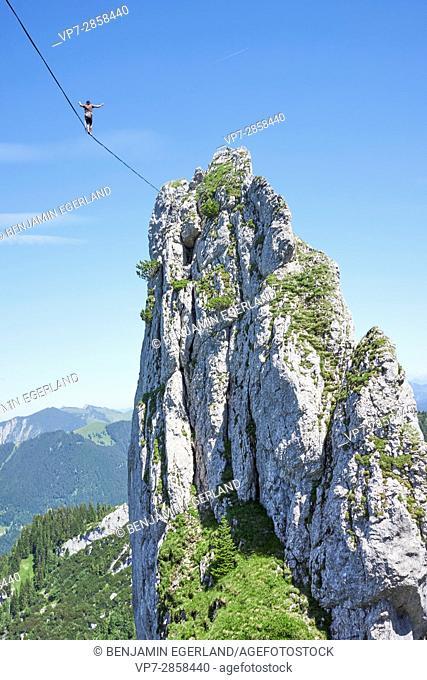 adventurous man balancing on highline slackline in Bavarian alps, near mountain Blankenstein, south of Germany