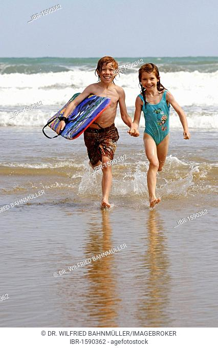 Children with boogyboard, and waves at the beach
