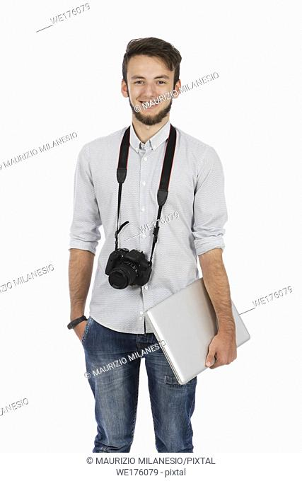 Nerd boy with camera around his neck and computer under his arm, he is standing in the studio and is wearing casual clothes