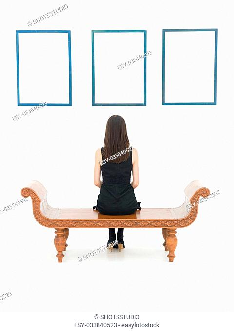 rear view of woman sitting on a wooden bench looking at empty blue frames displayed on a white wall in front of her