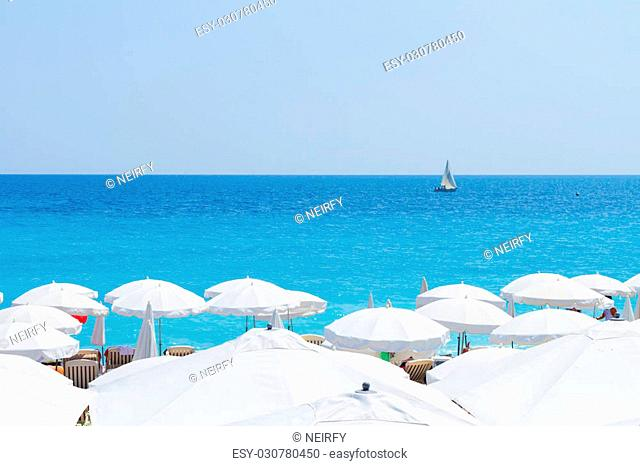 turquiose water of cote dAzur over white beach umbrellas, France