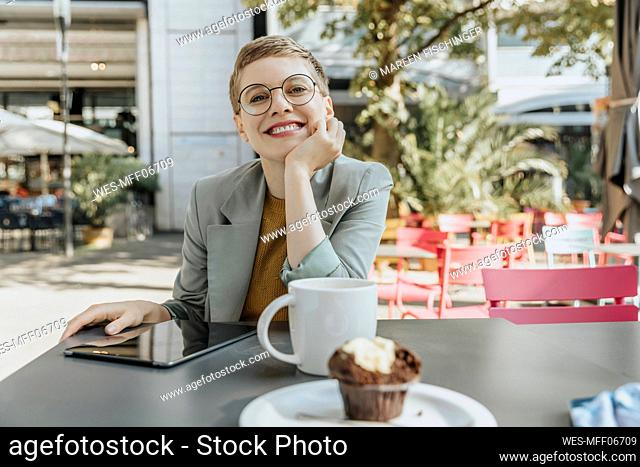 Woman with hand on chin sitting in sidewalk cafe