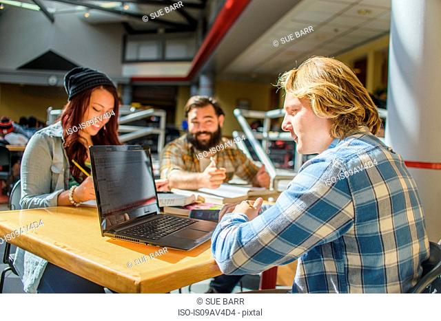 Three adult college students working at classroom desk