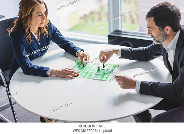 Businesswoman and businessman playing table football in office