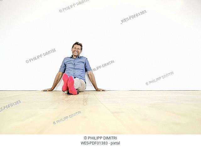 Mature man sitting on ground in empty room