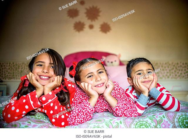 Children wearing pyjamas lying on fronts on bed chin in hands looking at camera smiling