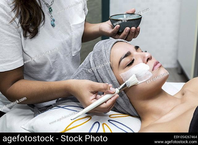 Woman receiving facial treatment in massage center with master applying cleansing mask on face skin