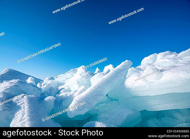 Closeup ice that covered with white snow. Water in the lake became frozen during winter period. Lake Baikal, Russia