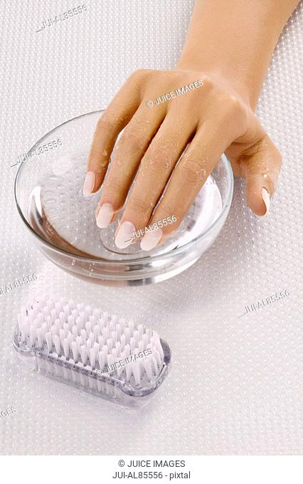 Close up of woman's hand in bowl of water next to nail brush