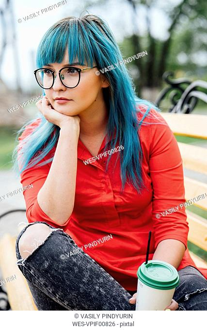 Portrait of young woman with dyed blue hair sitting on a bench with beverage