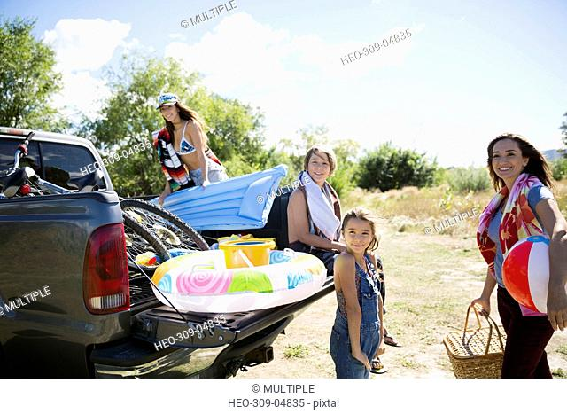 Portrait smiling family with beach equipment at sunny truck bed
