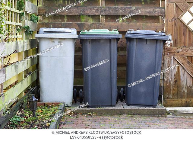 Three rolling trash cans in a dutch garden - Separating trash