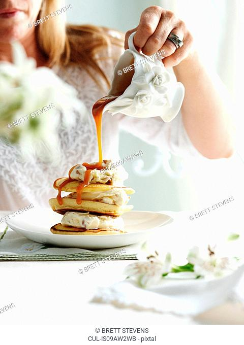 Woman pouring toffee sauce from ornate jug on stack of pikelets
