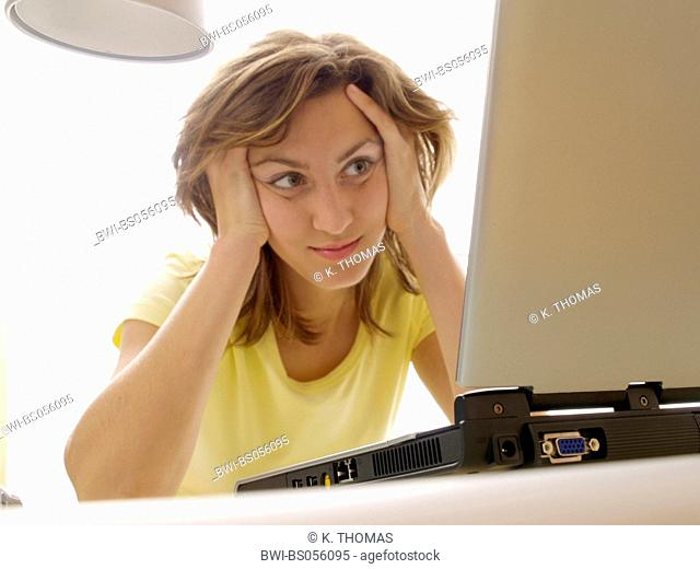 young woman / twen, sitting in front of the laptop, looking full of expectation on the monitor