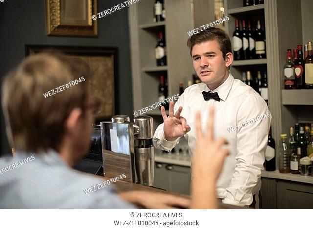 Barkeeper behind bar taking an order