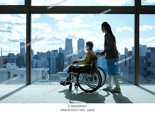 Care worker assisting senior couple in wheelchair