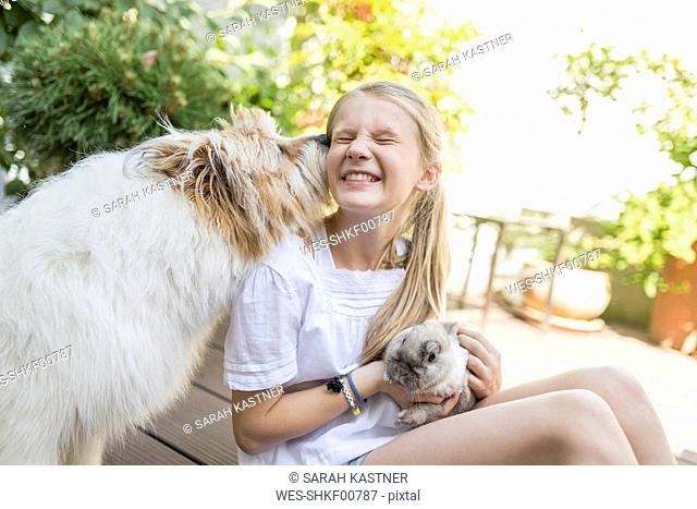 Happy girl with rabbit and dog outdoors