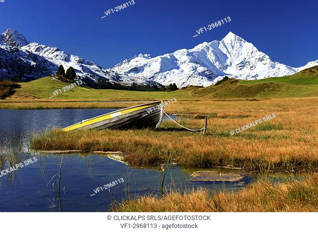 A boat at the shore of the small lake Lai da Vons, with Piz Tambo mirrroing into the lake, Sufers, Grisons, Switzlerand