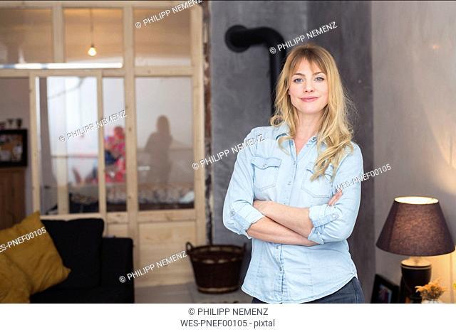 Portrait of confident blond woman at home