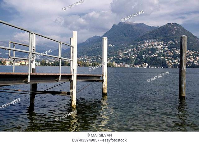 Alpine lake and a jetty with mountain and blue sky with clouds
