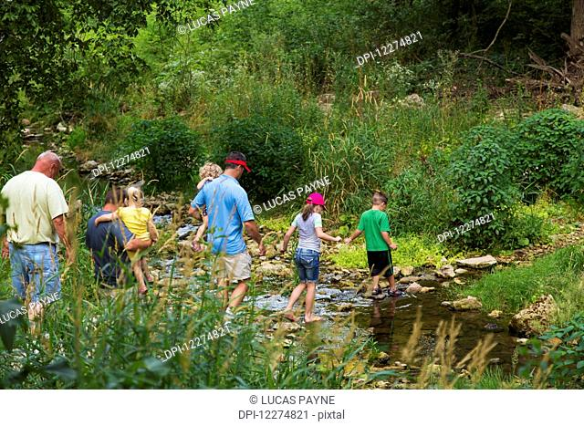 Family crossing Bear Creek on hiking trail leading to the Ice Cave at Bixby State Preserve, near Edgewood; Iowa, United States of America