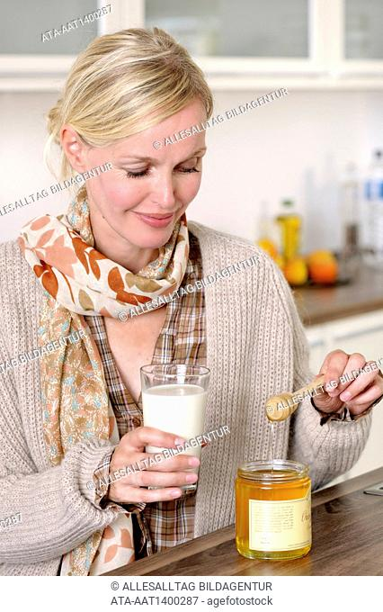 Woman is drinking hot milk with honey