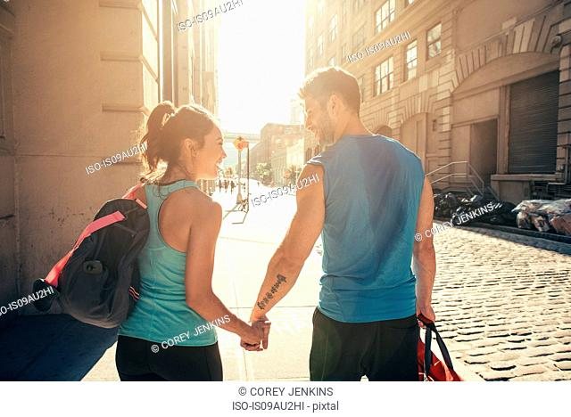 Young couple on street returning from training