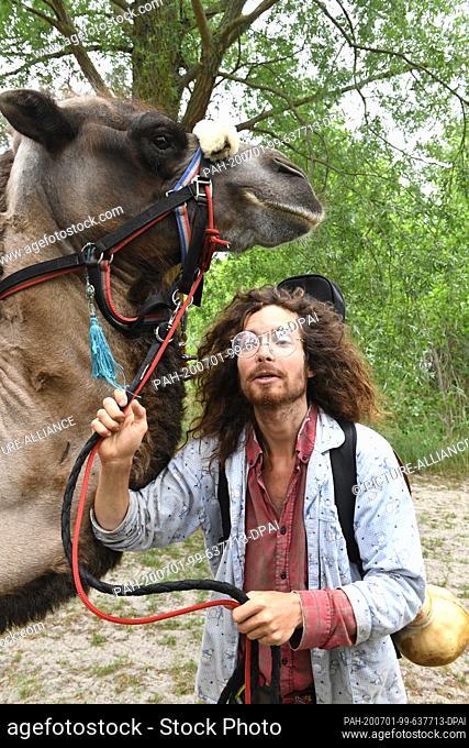 01 July 2020, Mecklenburg-Western Pomerania, Ueckermünde: Sebastien Arz walks with a camel through Ueckermünde. A man, a woman