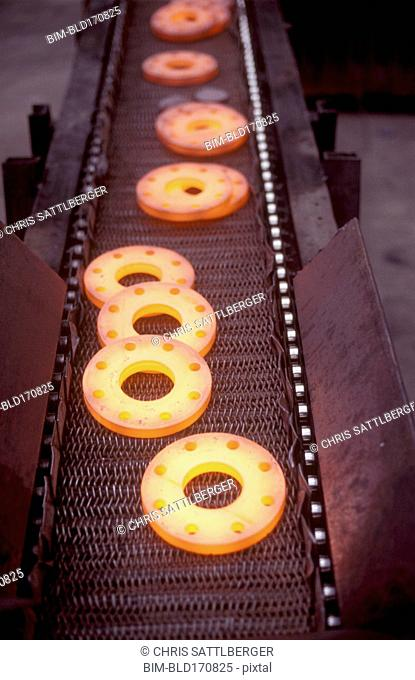 Glowing metal manufactured pieces on conveyor belt