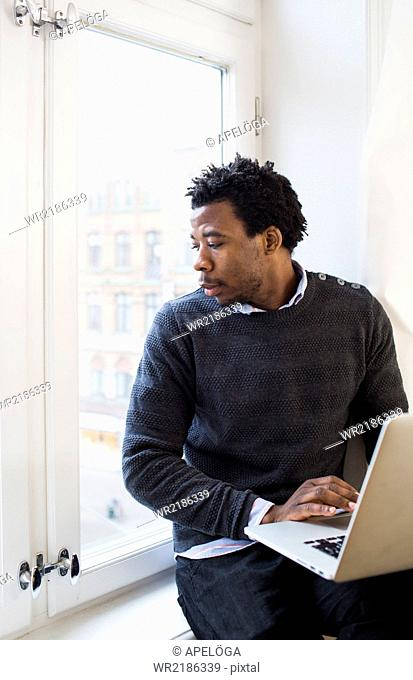 Young businessman using laptop while looking through window