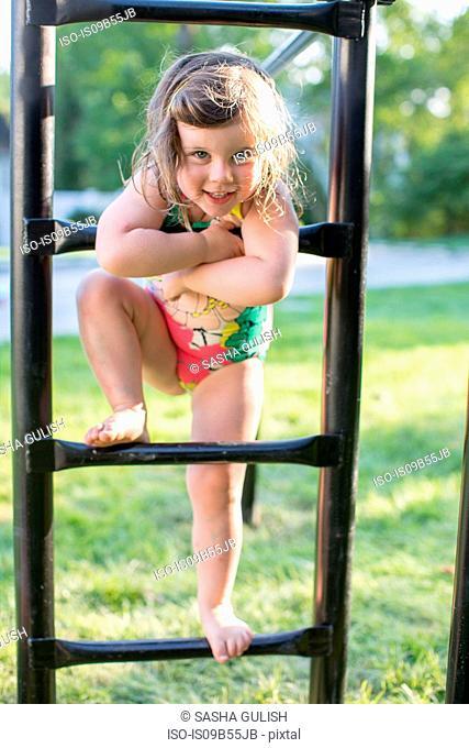 Portrait of girl in swimming costume standing on garden climbing frame