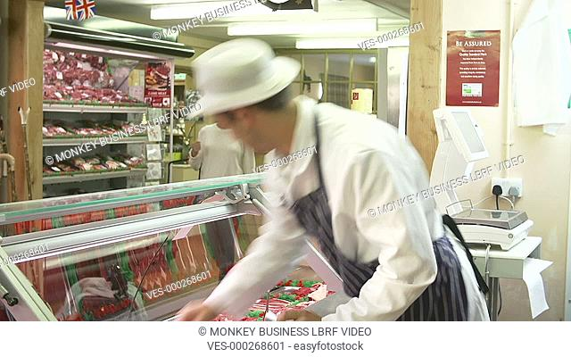 Woman asks butcher about selection of meat on display before selecting her purchase.Shot on Sony FS700 in PAL format at a frame rate of 25fps
