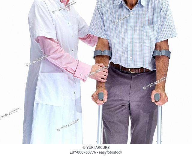 Mid section of nurse helping a man on crutches against white background