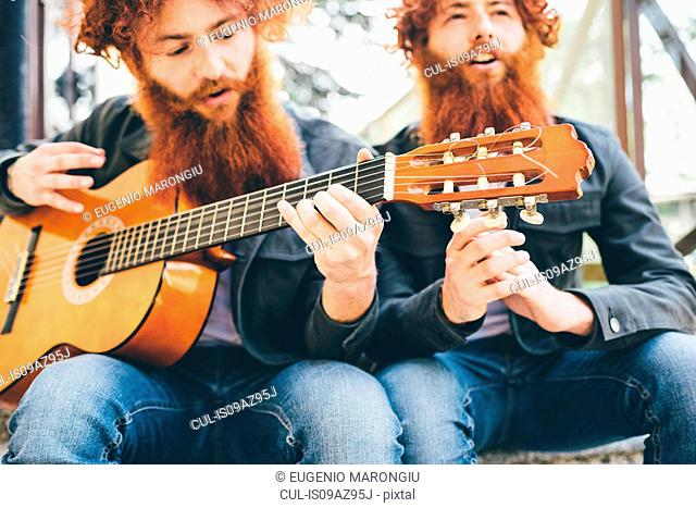 Young male hipster twins with red beards sitting playing guitar