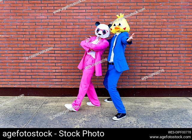 Man and woman wearing vibrant suits and animal masks posing together in front of brick wall