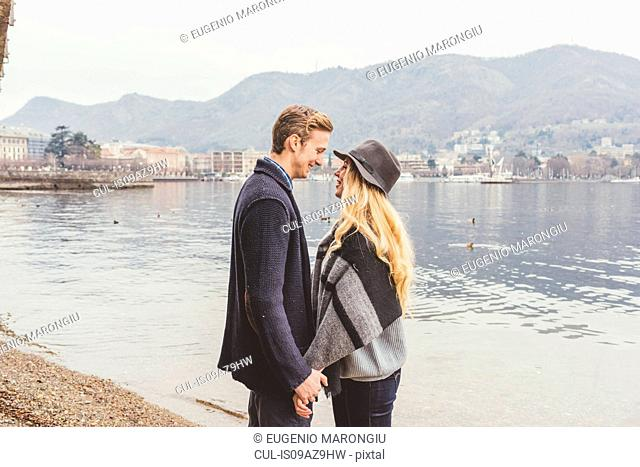 Romantic young couple face to face at misty Lake Como, Italy