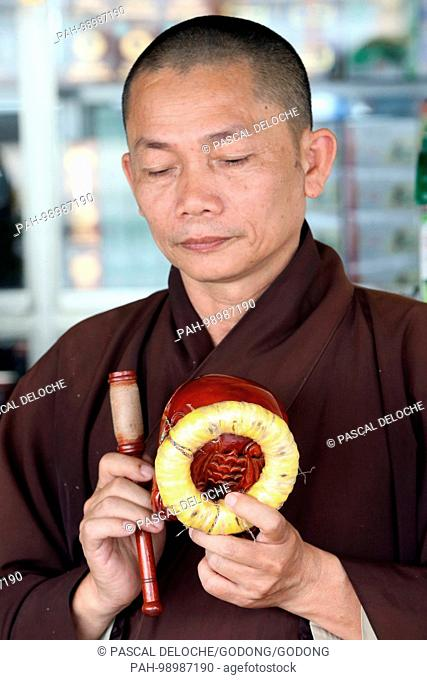Buddhist ceremony. Monk playing on a wooden fish (percussion instrument). Danang. Vietnam. | usage worldwide. - Danang/South Central Coast/Vietnam