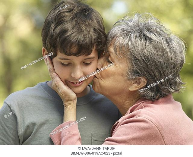 Hispanic grandmother kissing grandson on cheek