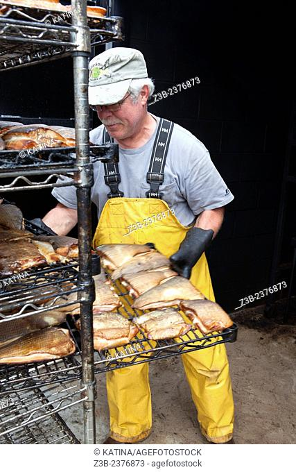 An employee in the smokehouse smokes freshly caught whitefish at Carlson's, a 5th generation fishing company in the Leland Historic District (Fishtown), Leland