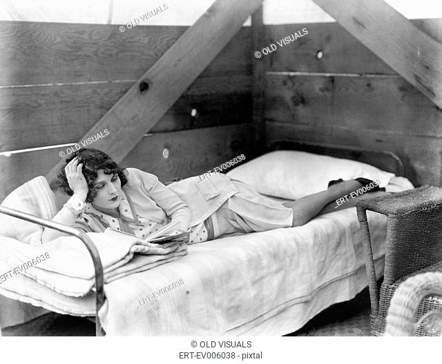 Woman stretched out on a cot reading a book All persons depicted are not longer living and no estate exists Supplier warranties that there will be no model...
