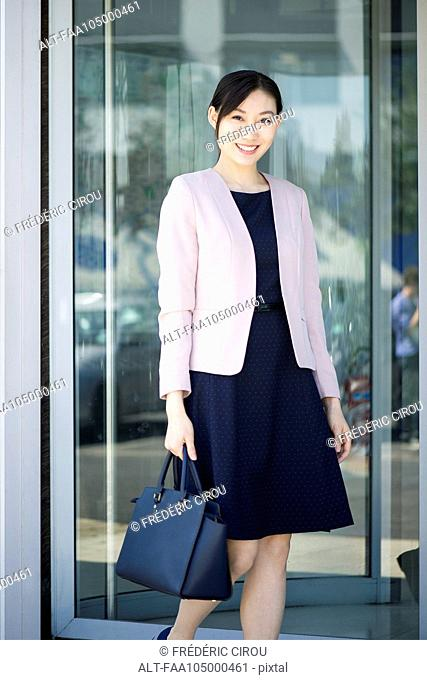 Businesswoman exiting building, smiling cheerfully