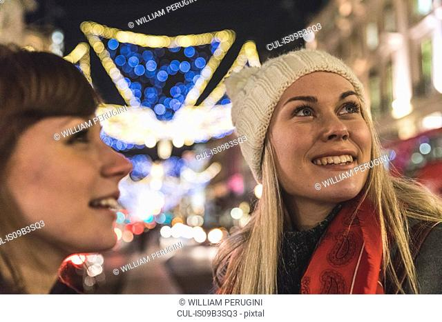 Two female friends standing in illuminated street at night