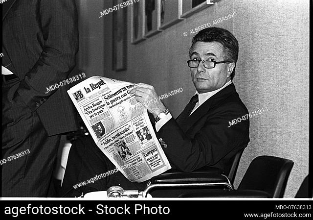 Italian writer, journalist, poet, theater critic and politician Alberto Arbasino reads the newspaper sitting on an armchair