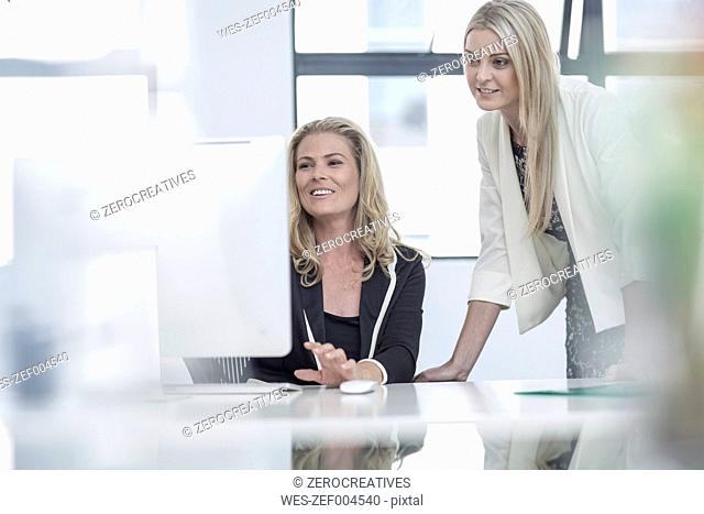 Two businesswomen in office working together